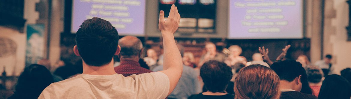 Church worshippers with lyrics projected onto big screens